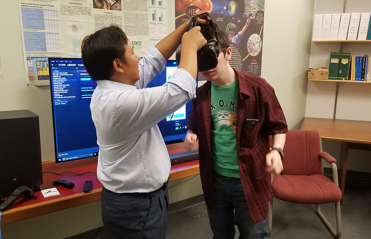 Professor putting VR goggles on student